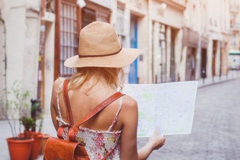 A tourist walking around a city with a map