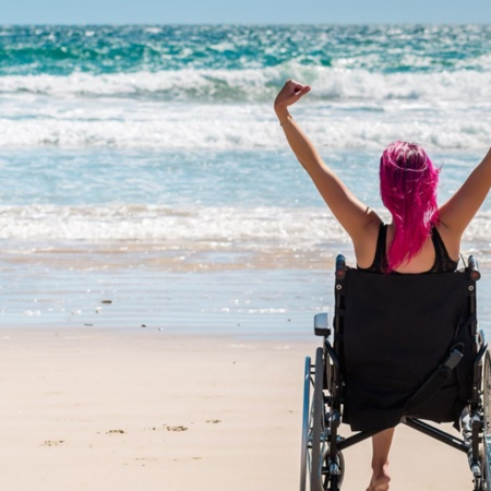 Tourist in a wheelchair enjoying the beach