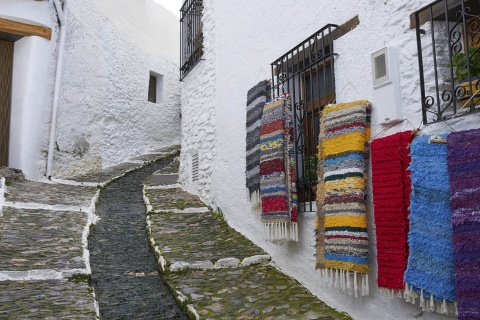 A typical street in Pampaneira (Granada), adorned with the traditional banners of La Alpujarra