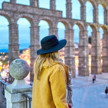 Girl looking at the Roman aqueduct of Segovia
