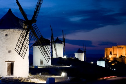 View of the windmills at night, with Consuegra Castle in the background. Toledo