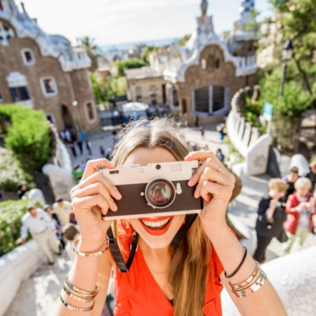 Girl smiling as she takes a photo in Park Güell, Barcelona