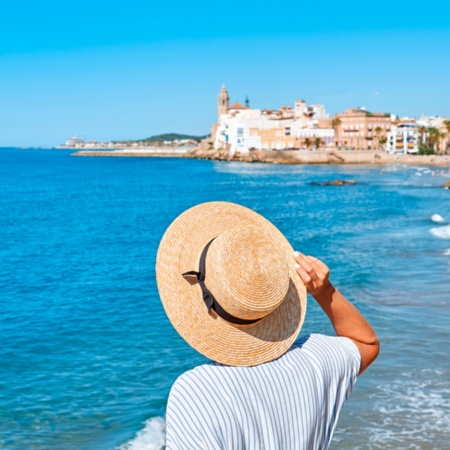 Woman looking at the sea and the church of Sant Bartomeu in Sitges