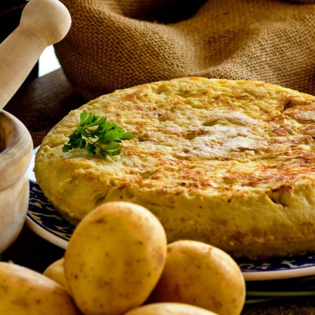 Spanish omelette with products to make it and a mortar