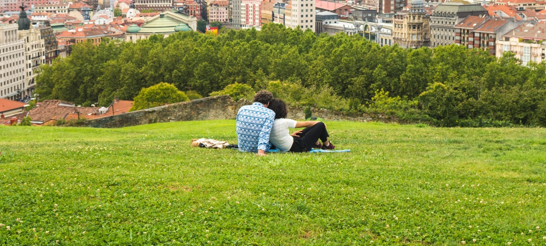 Couple admiring a lovely view of the city from the hillside park above the old quarter