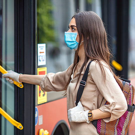 Girl wearing a mask and getting on a bus