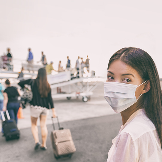 Girl wearing a mask and getting onto a plane