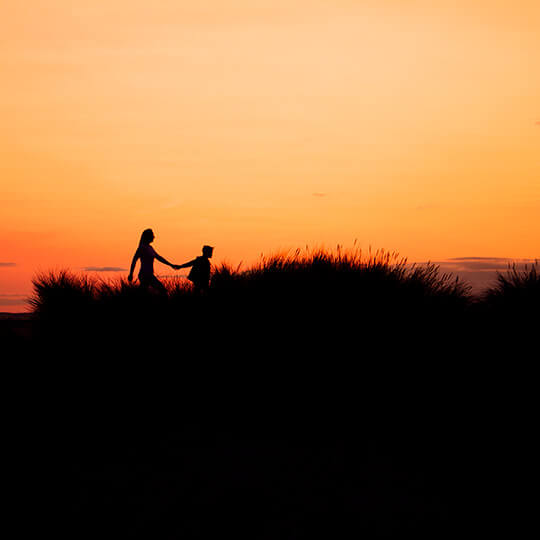 A mother and her son walking on a dune