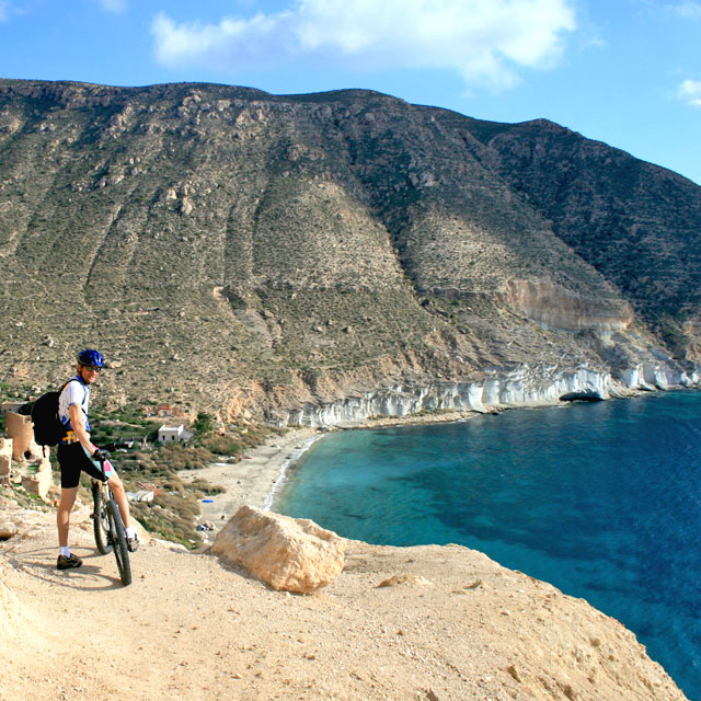 Cyclist looking at a cove in Cabo de Gata, Almería