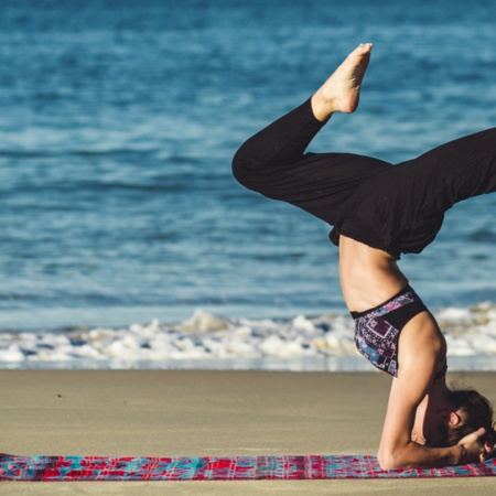 Girl practising yoga on the beach